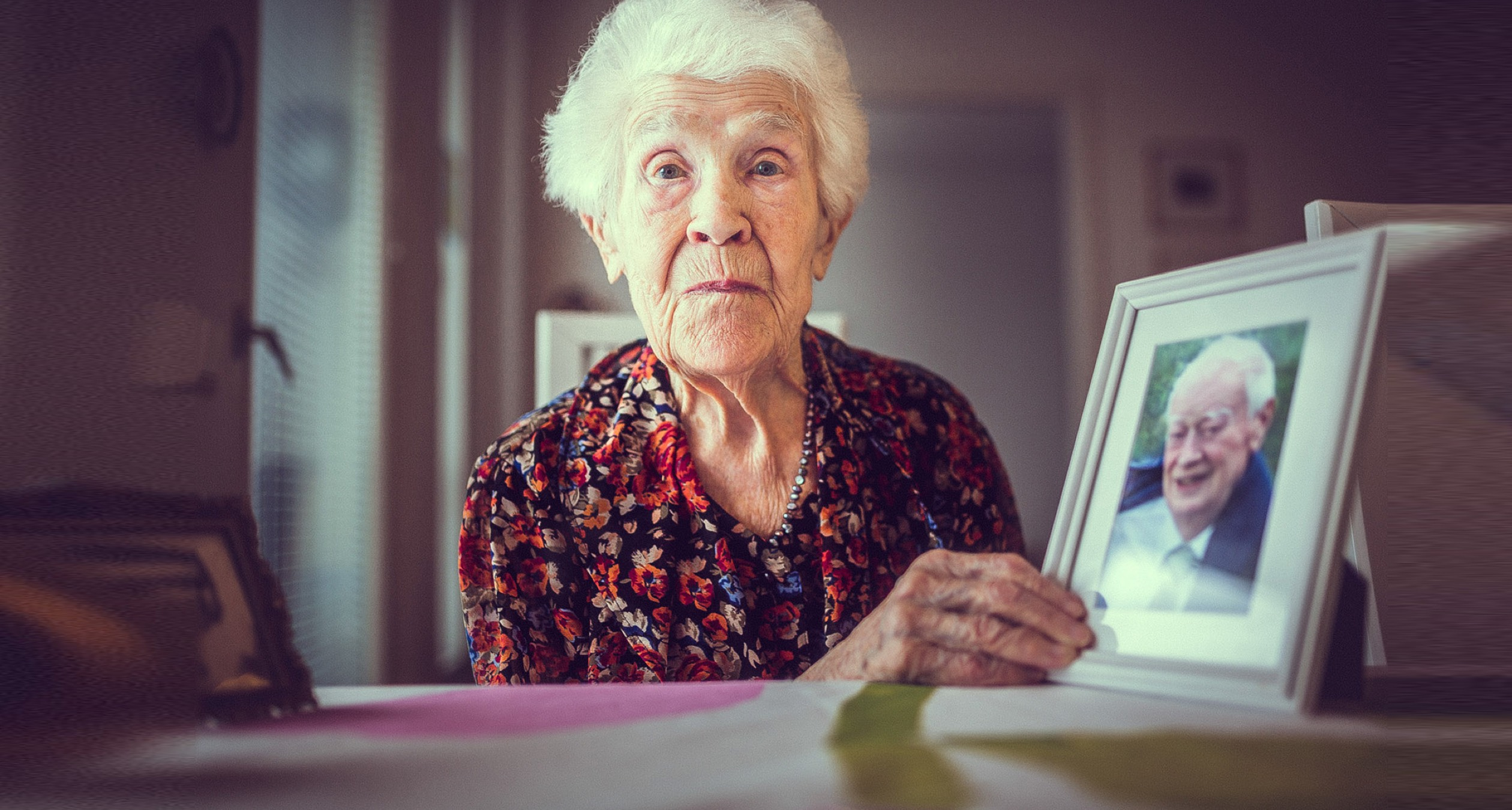 Elderly Woman Holding Image of Husband