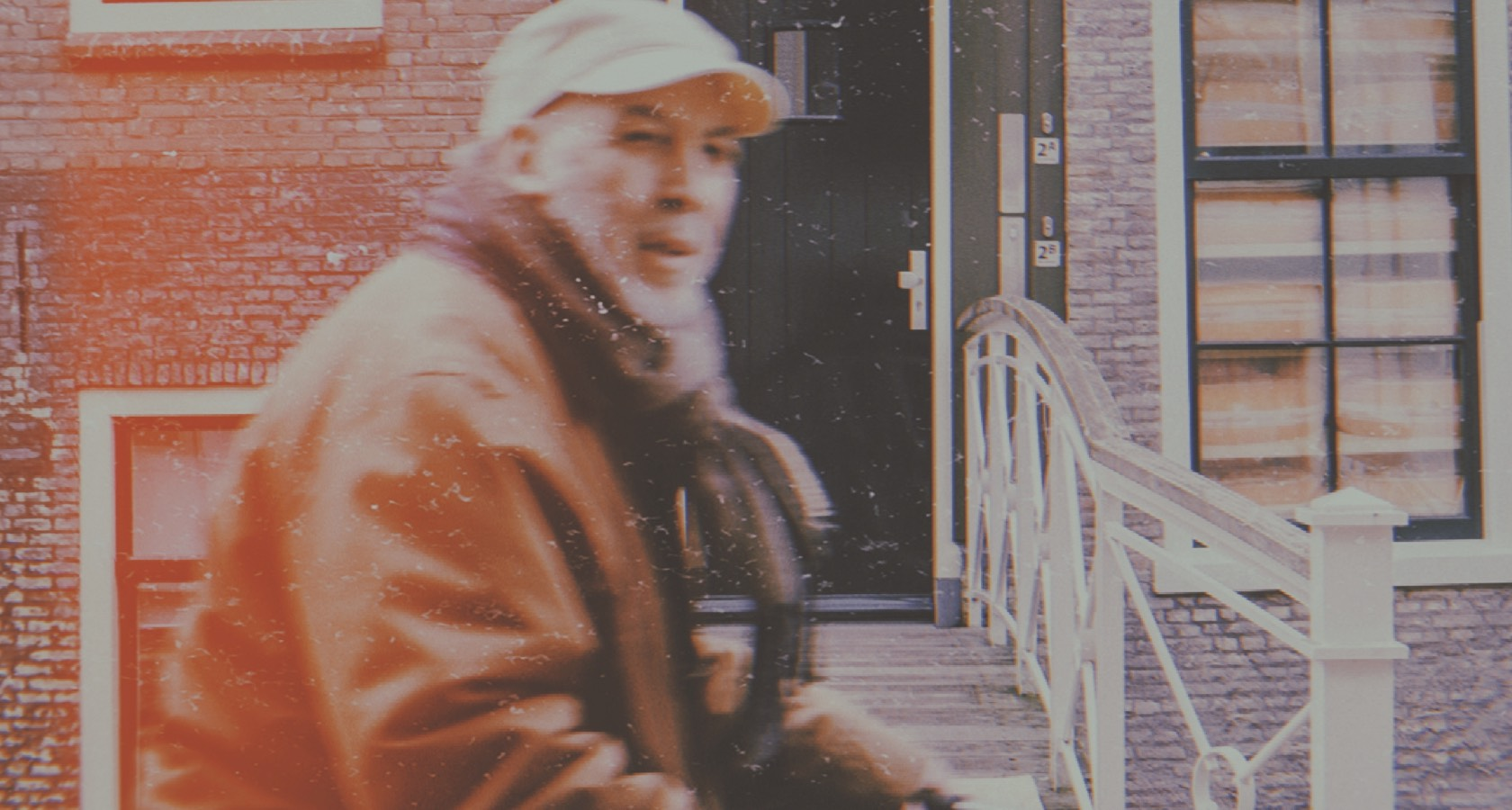 Elderly Man wearing a scarf, coat, and hat Outside in a City