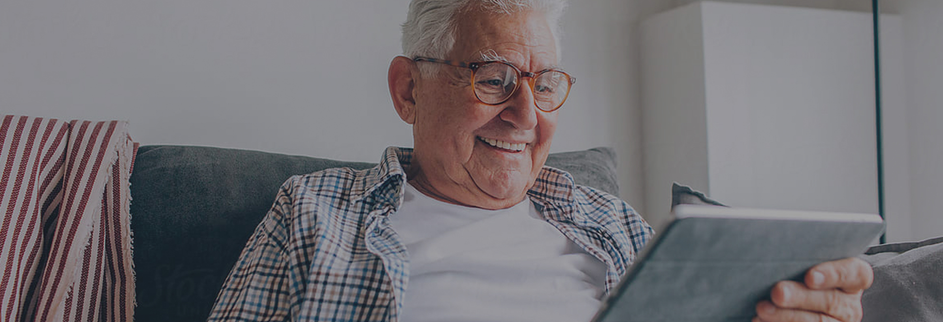 Elderly man sitting on couch looking at ipad