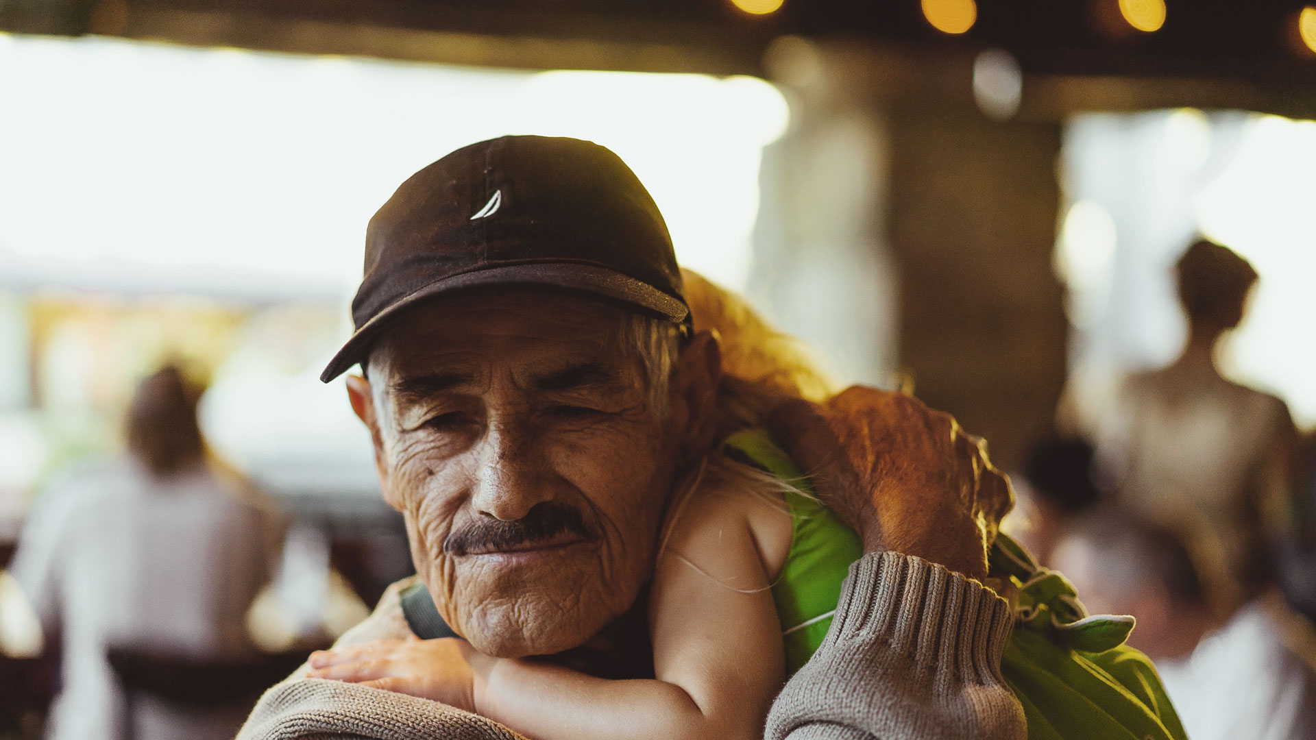 elderly man holding sleeping child