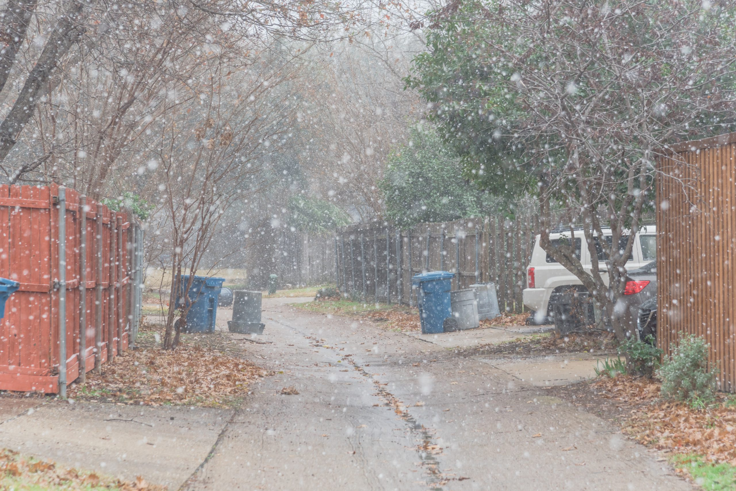 Snow falling in back alley of Texas community